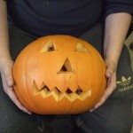 Hands holding a carved out pumpkin